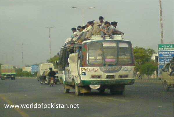 Passengers riding on top of a bus (on the roof), a common sight in Karachi.